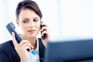 Beautiful young female executive holding telephone handset and cell